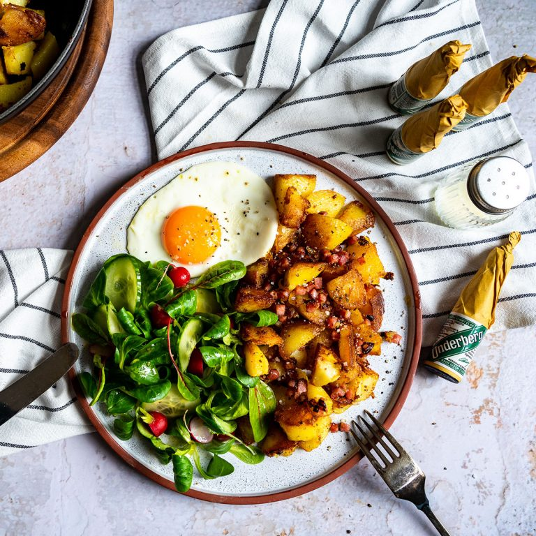 Fried potatoes with fried egg and salad