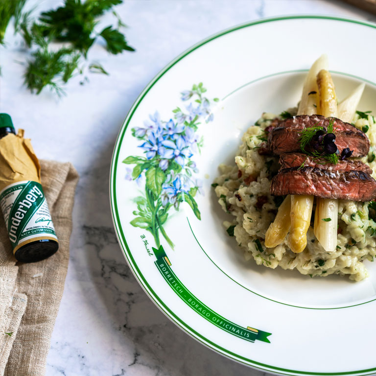 Herb-bacon risotto with white asparagus and beef strips