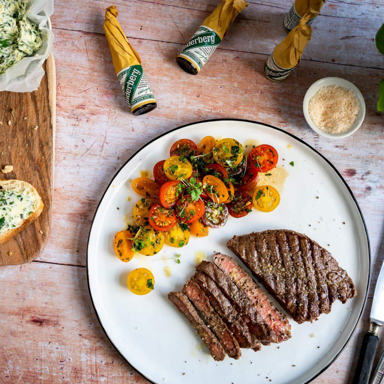 Steak with herb butter, tomato salad and baguette